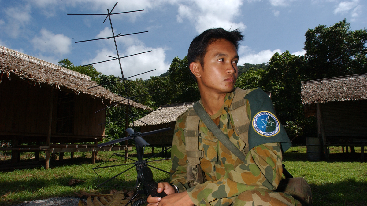 Soldier holding an antenna with straw roof huts in background