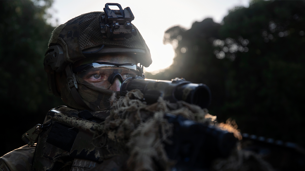 Australian soldier looking down his weapon, with full gear on.